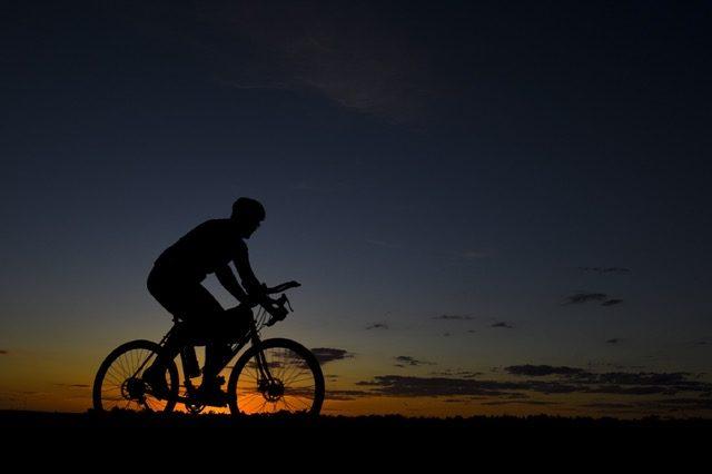 man-riding-bicycle-during-nightfall